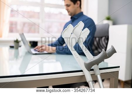 Close-up Of Crutches Leaning On Table In Front Of Handicapped Man Working