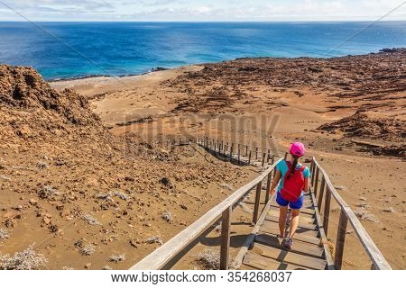 Galapagos tourist hiking enjoying famous Bartolome Island. Travel vacation adventure woman on hike to viewpoint and visitor site of landscape.