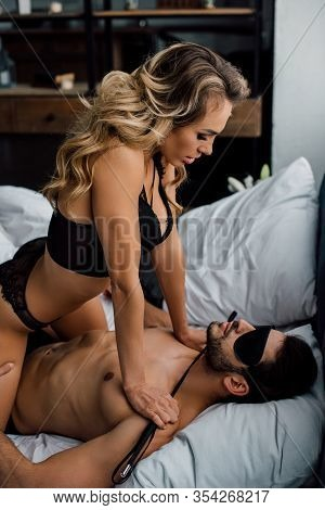 Side View Of Submissive Man In Eye Mask Touching Dominant Woman With Flogging Whip On Bed