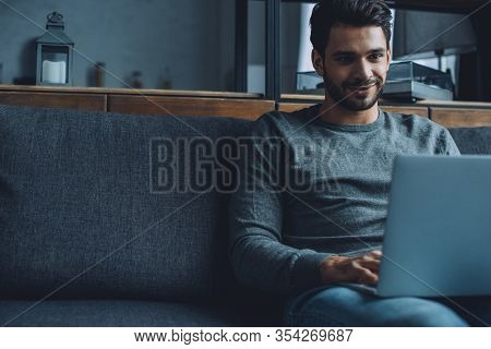 Smiling Man Watching Pornography On Laptop While Sitting On Couch In Living Room