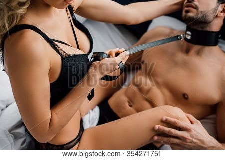 Cropped View Of Dominant Woman Holding Bdsm Leash On Shirtless Man On Bed Isolated On Black