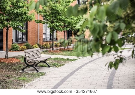 Paved Path, Bench And Brick Building Seen Through Green Leaves. Green City Neighborhood In Spring.