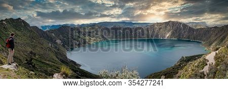 Caucasian Backpacker Looking At A Marvelous Lake Inside A Volcano Named Quilotoa At Sunset. Ecuador,