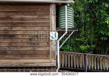 A Weathered Slat Timber Wall Of A Bushland Toilet Building With Raised Water Tank And Sign That Pets