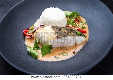 Gourmet fried skrei cod fish Thai curry with jasmine rice and chili as closeup on a modern design plate
