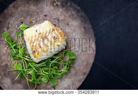 Gourmet fried European skrei cod fish filet with purslane lettuce and herbs as top view on a modern design plate with copy space right