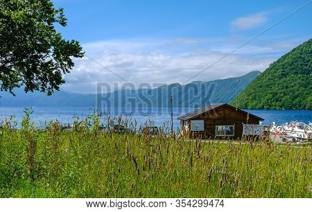 The Lake House ,great View Of Mountain Lake, Green Grass Foreground With Lake And Mountain View Back