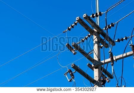 High Voltage Electric Pole And Transmission Lines With Clear Blue Sky. Electricity Pylon. Power And
