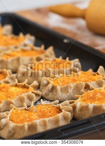 Stage Of Preparation Of Karelian Pies. Pies Are Located On A Baking Sheet, Ready For Baking. Dish Of