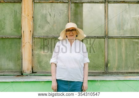 portrait of senior woman with hat near the old window