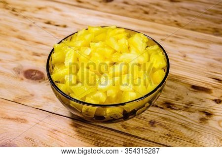 Glass Bowl With Chopped Pineapple On Rustic Wooden Table