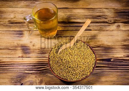 Cup Of Yellow Tea (methi Dana) And Plate With Fenugreek Seeds On Rustic Wooden Table