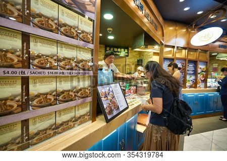 SINGAPORE - JANUARY 20, 2020: woman ordering foot at a food court in the Shoppes at Marina Bay Sands