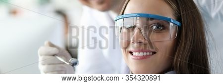 Portrait Of Beautiful Female Looking At Camera With Gladness And Smile. Stomatologist Examining Teet
