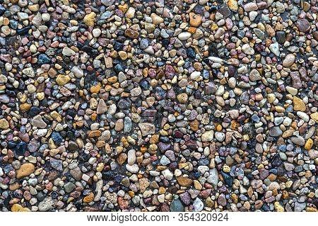 Background Of Small Multi-colored Crushed Stone. Fine Sea Pebbles Texture. Small Multi-colored Pebbl