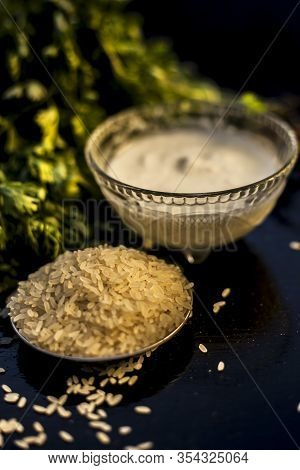 Coriander Face Mask For All Skin Types On The Black Wooden Surface Along With Some Rice, And Yogurt.