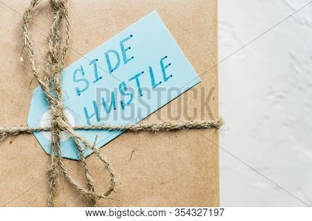 Side Hustle Written On Blue Tag Against Gift Box Wrapped In Recycled Paper Background.