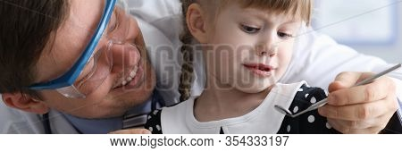 Portrait Of Scared Child Visiting Dental Clinic. Smiling Doctor Calm Down Examining Oral Cavity Of G