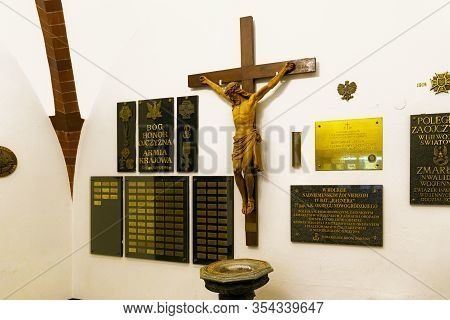 Sopot, Poland - December 20, 2017: Wooden Crucified Jesus Christ And Patriotic Plaques On The Wall D