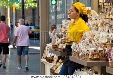 Barcelona, Spain - May 16, 2017: Unknown Young Woman Selling Different Cookies And Other Sweets Prod
