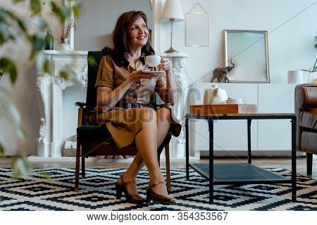 Middle Aged Brunette Woman Drinking Tea In Drawing Room And Enjoying Slow Breakfast And Tasty Breakf