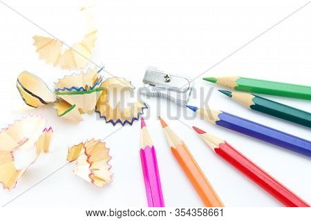 Multi-colored Wooden Pencils, A Metal Small Sharpener And Sharpening Shavings. On A White Isolated B
