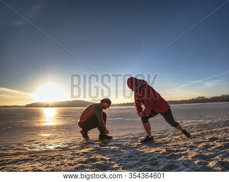 Heterosexual Couple, Woman And Man Working Out Near Winter Lake. Cold Morning Exercise On The Lake B