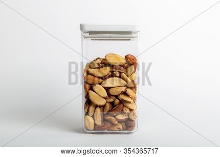 Raw Brazil Nuts Inside A Transparent Plastic Container With A White Background, Also Called Bertholl