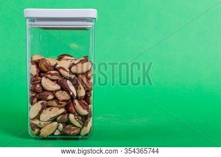 Brazil Nuts Raw Inside A Transparent Plastic Container With A Green Background, Also Called Bertholl
