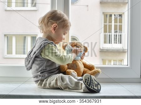 Child In Home Quarantine Playing At The Window With His Sick Teddy Bear Wearing A Medical Mask Again