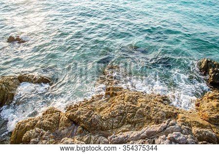Natural Stone Beach With Splashing Wave Sea On Sunny Day At Koh Larn Island.