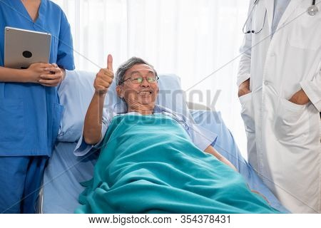 Asian Patient Man Smiling And Lying Down On Hospital Bed In The Hospital Room