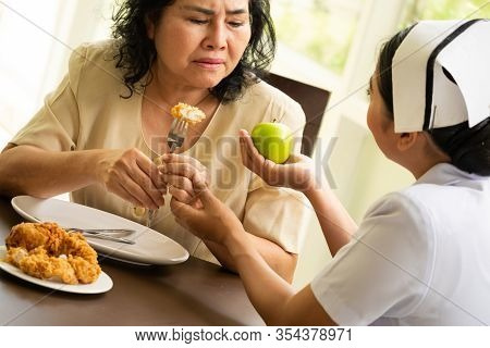 Nurse Suggesting Adult Female Patient To Eat Apple Instead Of Chicken Fried.