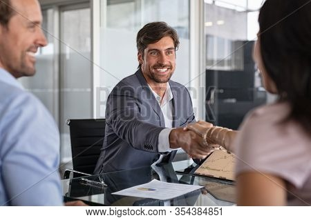 Businessman handshake during meeting, signing agreement for financial investment. Handshake of a manager with mature couple. Happy financial advisor shaking hands with his client after insurance deal.