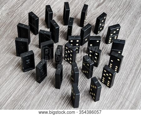 Black Dominoes On A Light Wooden Table Stand In A Row, Selective Focus, Black Old, Vintage Dominoes