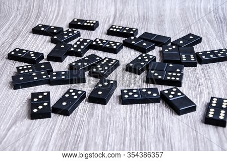 Black Dominoes On Wooden Background, Closeup Scattered Dominoes On A Gray, Wooden Table. Board Game,