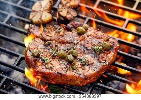 Grilled Pork Steak Pork Neck  With Addition Of Capers And Aromatic Herbs On The Grill Plate, Close U