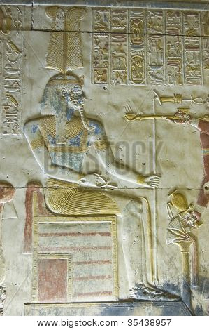 Bas relief carving of the ancient Egyptian god Amun.  Coloured blue with a headdress of ostrich feathers.  Wall of Abydos Temple, near el Balyana, Egypt.  On public display for over 2,000 years. poster
