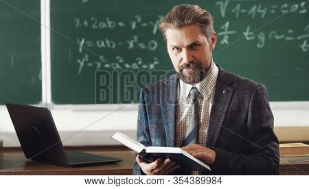 Glad Adult Mathematician In Formal Wear Holding Open Book Looking Camera On Chalkboard Background