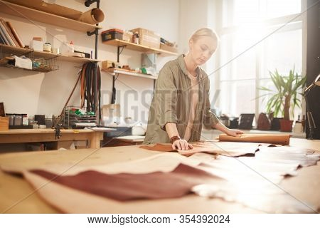 Young Woman Standing At Table In Her Workshop Rolling Out Leather Material For New Craftwork, Horizo