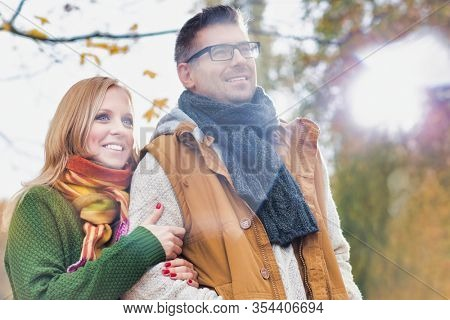 Portrait of attractive man and woman standing in park