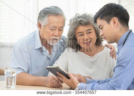 Elder Senior Old Asian Couple Meeting  Specialist Professional Caucasian Doctor Visit At Home Consul