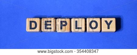 Deploy Word On Wooden Cubes On A Blue Background