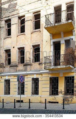 Ruined Dirty Facade. Broken Windows. Facade Of An Old Collapsing City House With Broken Window Block