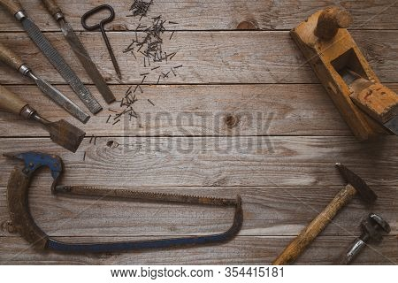 Vintage Woodworking Tools On A Wooden Background. Chisels, Raspers, Plane, Hammer, Hand Saw And Nail