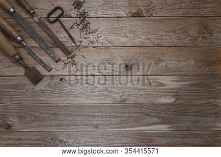 Vintage Woodworking Tools On A Wooden Background. Chisels, File, Puncher And Nails  Neatly Organized