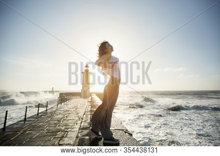 Beautiful asian woman walks along the railing of ocean promenade near the lighthouse with a foaming surf.