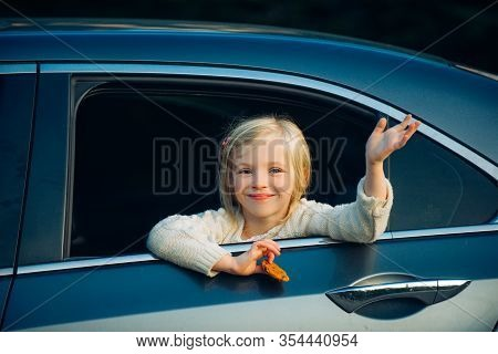 Cute Little Girl Traveling In The Car And Observing Nature From Open Window. Little Girl Waving Hand