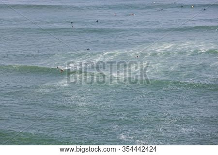 A Multitude Of Unidentifiable People Enjoying The Waves As They Surf In Full Wet Suits In The Cold W