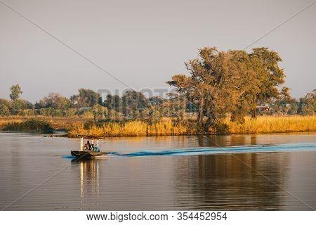 Chobe National Park, Botswana - August 1 2019: Small Tourist Game Spotting Boat Cruising On Chobe Ri